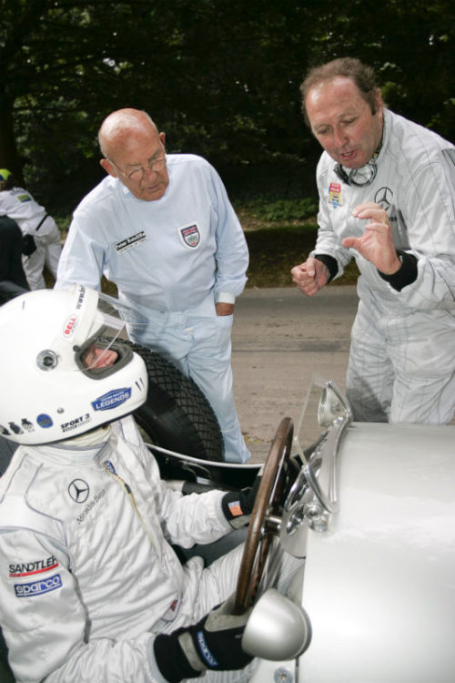 Sir Stirling Moss and Jochen Mass taking to fellow driver at the start line