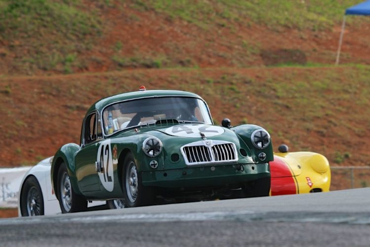 Carl George, 59 MGA followed by a Porsche and a Jaguar out of turn 5.