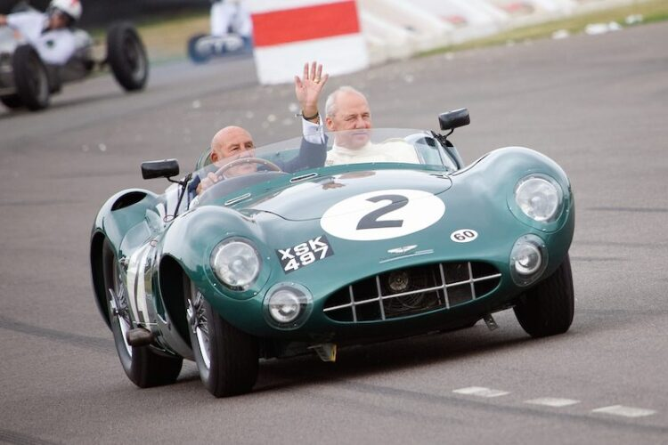 Sir Stirling Moss waves to crowd behind the wheel of Aston Martin DBR1