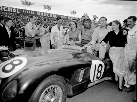 Duncan Hamilton, center, poses alongside his co-driver Tony Rolt and their wives, in their winning Jaguar, after winning the Le Mans 24 race, June 15 ,1953