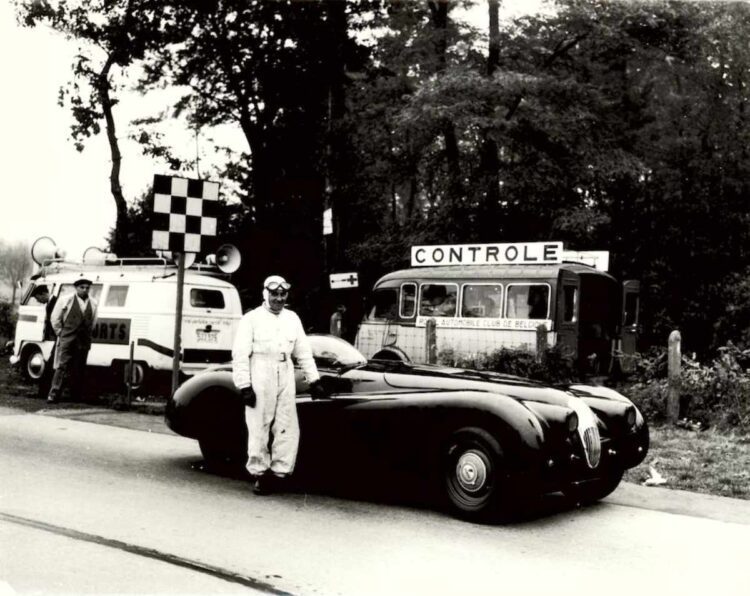 Norman Dewis standing next to the  modified Jaguar XK 120