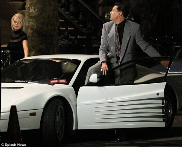 Leonardo DiCaprio with co-star Margot Robbie getting out of a Ferrari