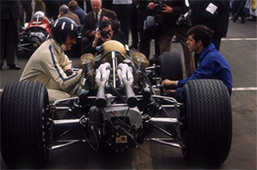 Graham Hill, (mid 1960s?). Hill crouches down alongside a racing car, talking to the driver. Graham Hill was one of the first Formula 1 drivers to become a television personality as well as a racing star. He made his debut at Monaco in 1958 and went on to win 14 Grands Prix, and was World Champion in 1962 and 1968. He joined Jim Clark at Team Lotus in 1967, and in 1969 won his last Grand Prix - his fifth triumph at Monaco. He broke both legs when he was flung from his car in the United States Grand Prix, and was killed in a plane crash in 1975 with five other members of his Embassy Hill team.