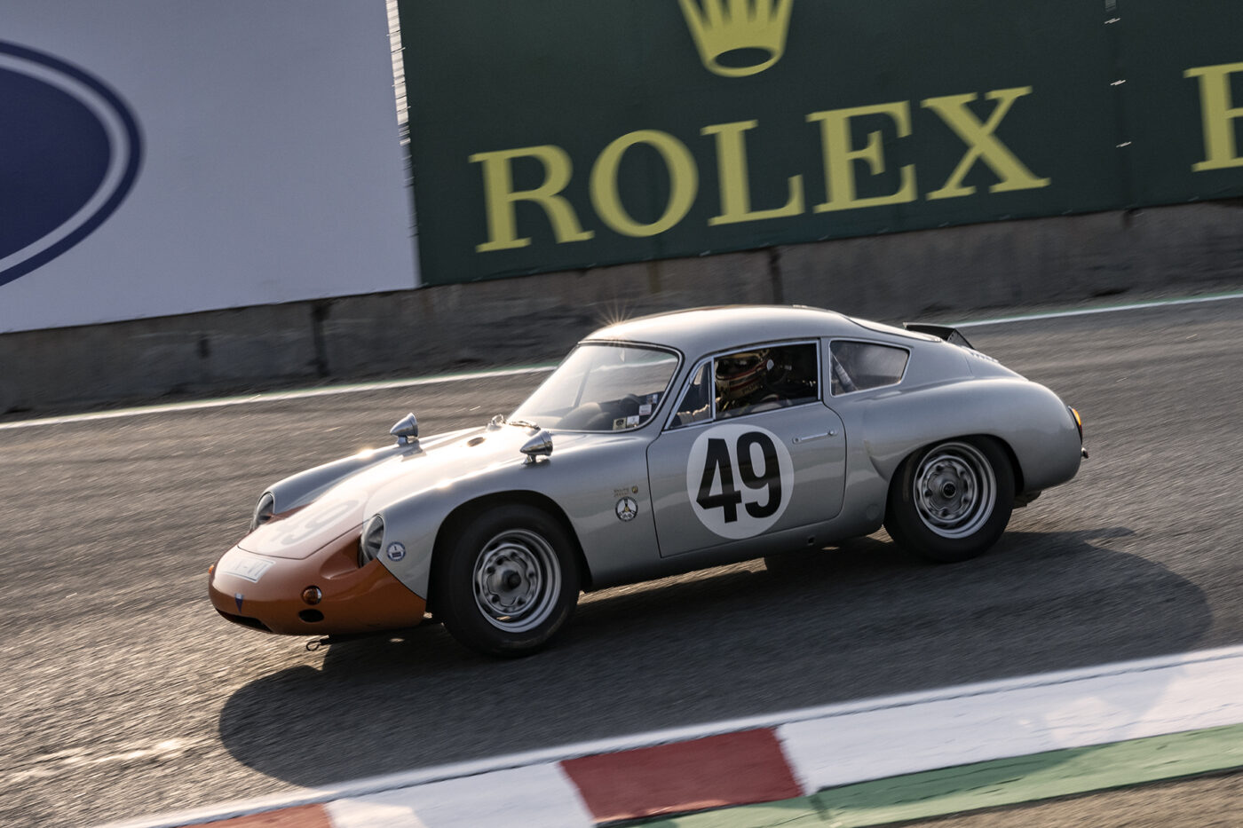 Early Saturday morning sun lights up Ranson Webster's 1961 Porsche Abarth Carrera 1966 as he approaches the Corkscrew. ©2021 Dennis Gray