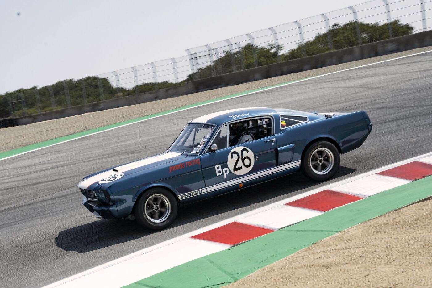 A 1966 Shelby GT350 4700 driven by John Linfesty tops the crest dropping into the Corkscrew. ©2021 Dennis Gray