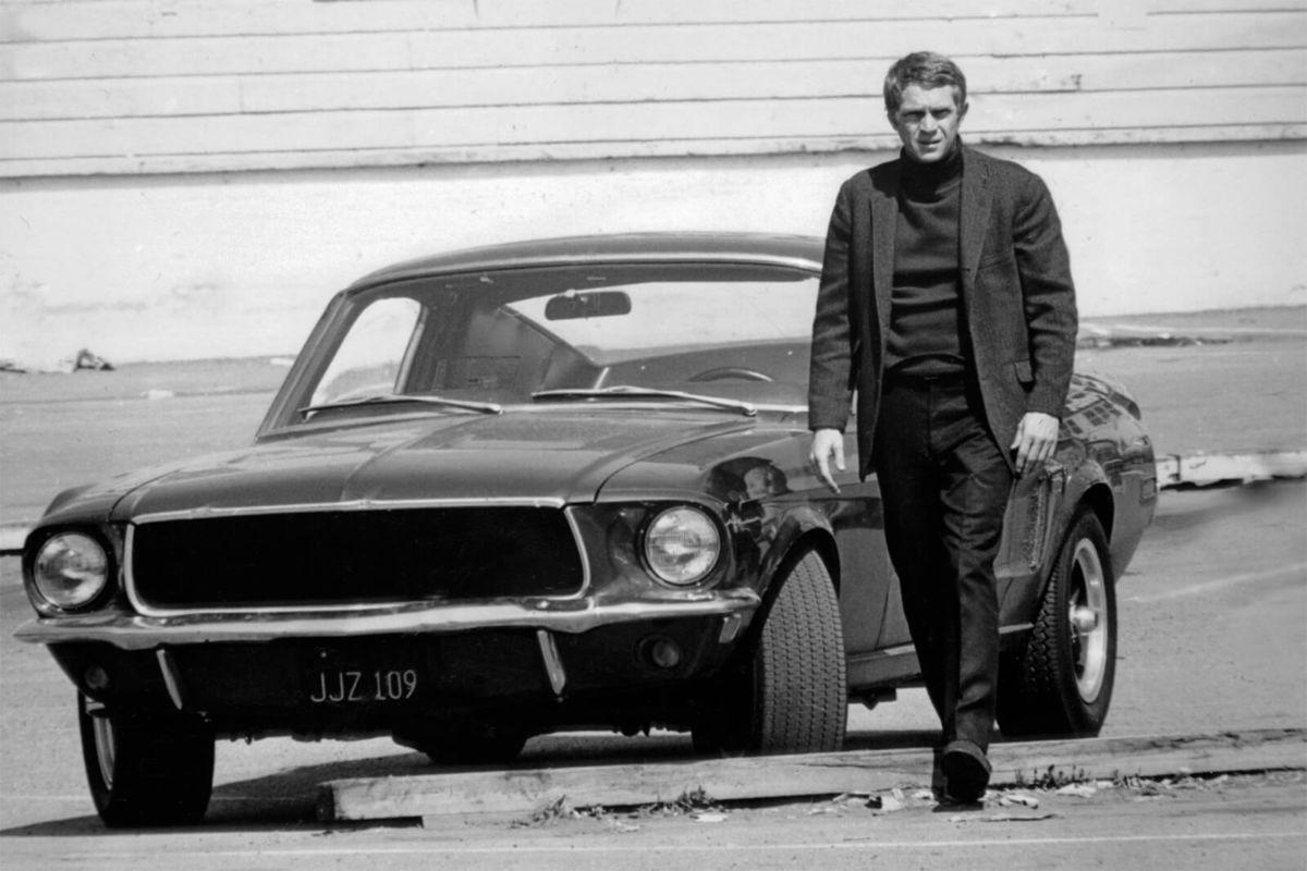 Steve McQueen standing in front of Ford Mustang Bullitt