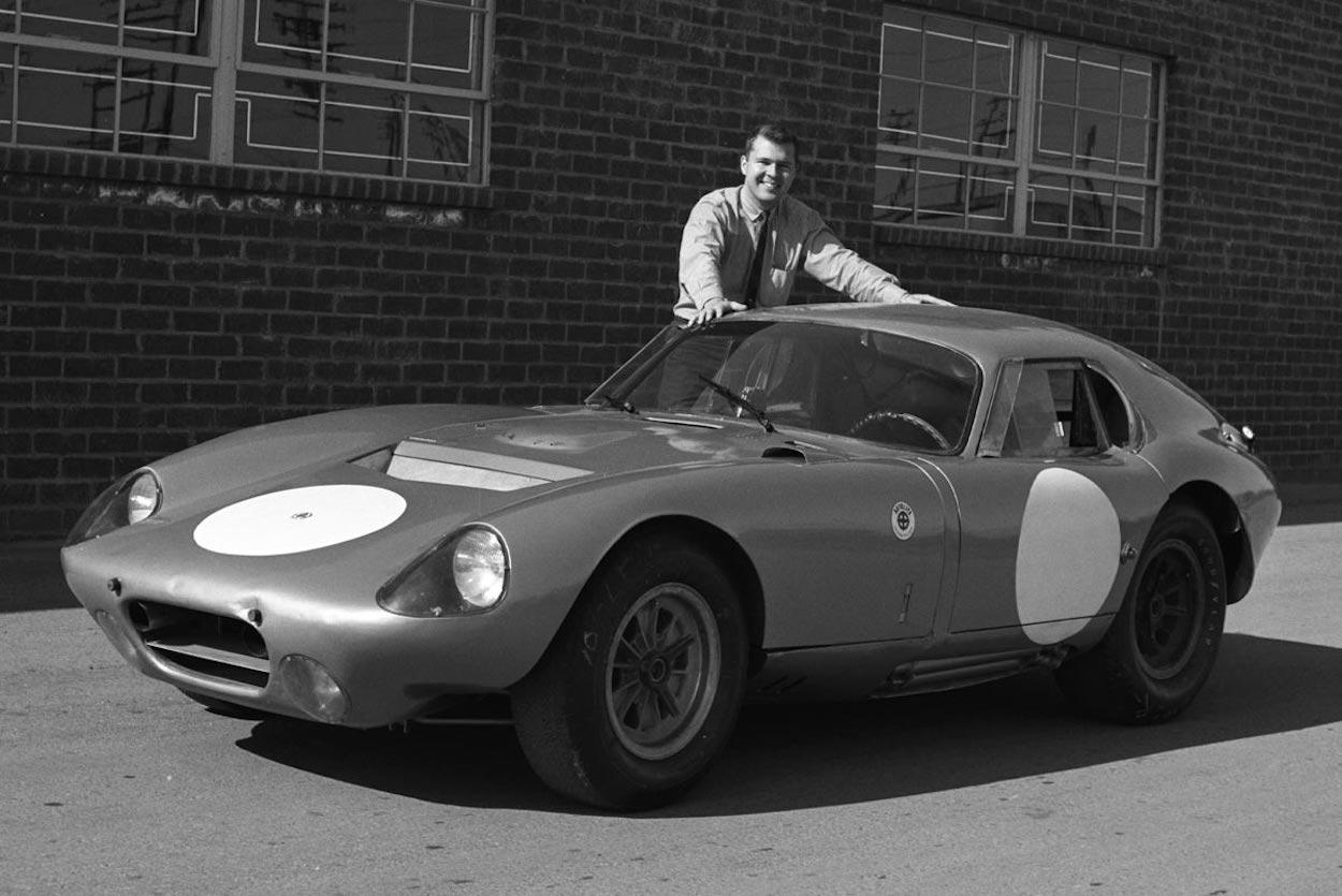 Young Peter Brock posing next to a Shelby Daytona Coupé