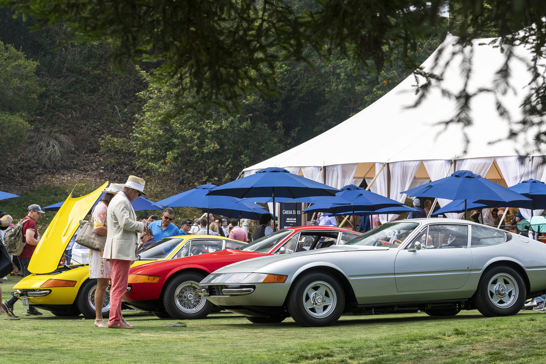 A group of cars at the Quail event with food pavilions in the background