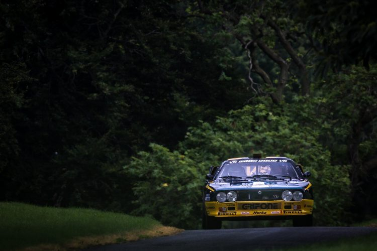 Lancia 037 in Olio Fiat livery emerging from a woodland section of the stage
