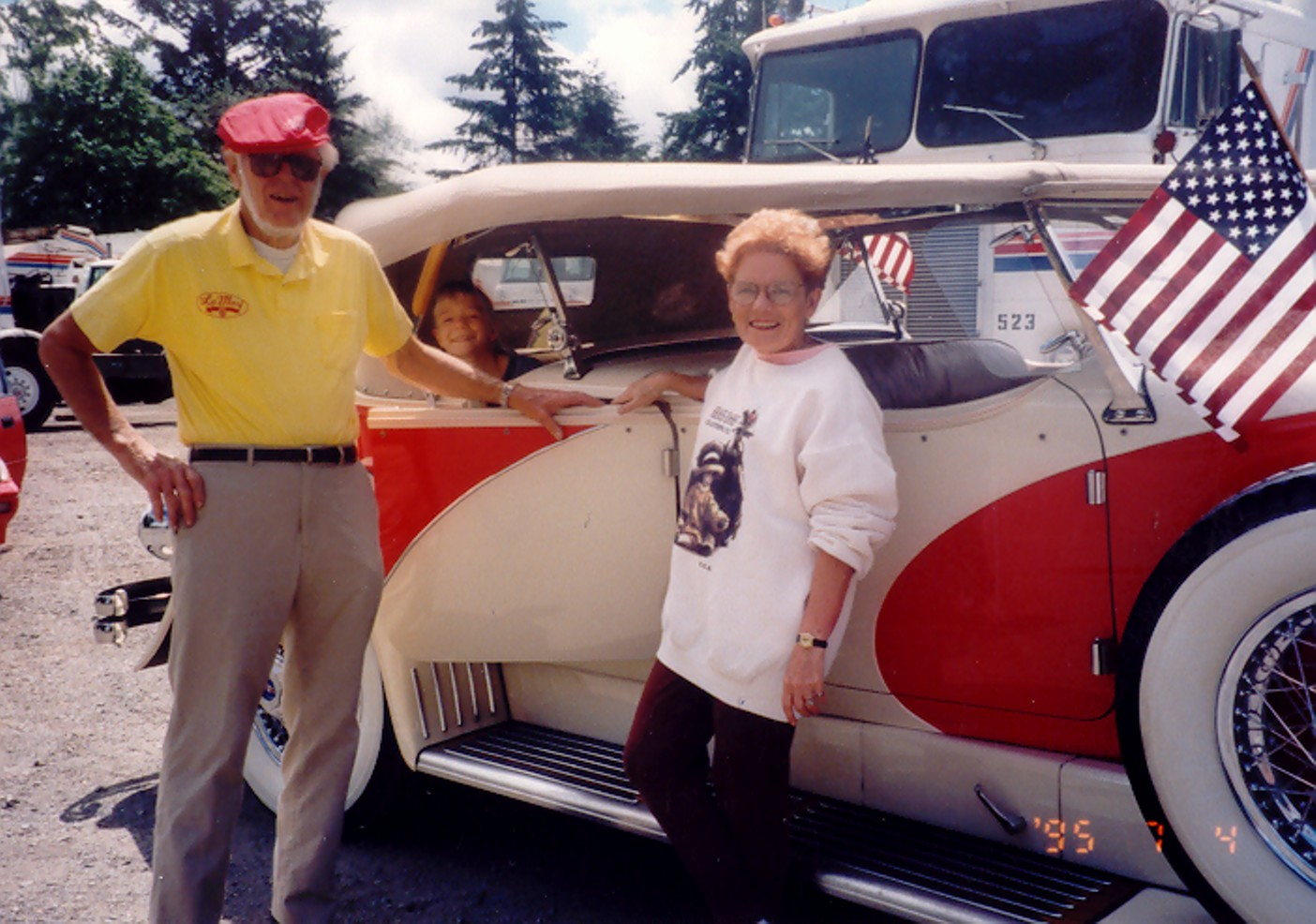 A photo of Nancy and Harold LeMay standing next to their Duesenberg car.